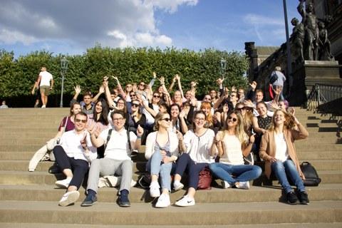 Gruppenfoto auf Treppe Brühlsche Terrasse, viele TeilnehmerInnen lachen und recken Hände in die Höhe, sonniges Wetter