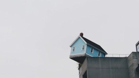 Ein Haus hängt halb über eine Klippe und droht zu fallen.