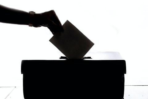 Hand, die einen Wahlzettel in eine Wahlurne wirft.