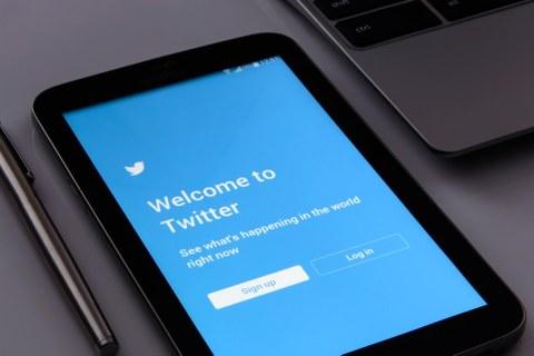 Ansicht des blauen Anmeldebildschirms der Twitter-App auf einem Handy, daneben liegt ein Stift bzw. ein Teil eines Laptops ist erkennbar.