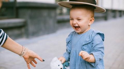 Auf dem Bild ist ein lachendes Kind zu sehen, welchem von einer erwachsenen Person ein Hut über den Kopf gehalten wird.