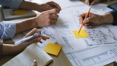 Zu sehen ist ein Tisch, auf dem mit Notizen versehene Blätter liegen. Darüber sind Hände von verschiedenen Personen zu sehen, die unter anderem Stifte halten.