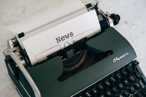 Zu sehen ist eine Schreibmaschine mit einem eingespannten Blatt Papier mit dem Schriftzug News.