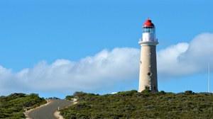 Zu sehen ist, ein weißer Leuchtturm mit rotem Dach auf einem Hügel.