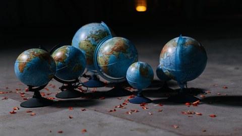 Zu sehen sind sieben Globen in unterschiedlicher Größe, welche auf einem grauen Fußboden stehen.