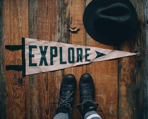 Zu sehen ist ein dreieckiges weißes Banner auf einem hölzernen Fußboden, bedruckt mit dem Wort Explore. Unter dem Banner sind ein paar Schuhe zu sehen, daneben ein Hut.