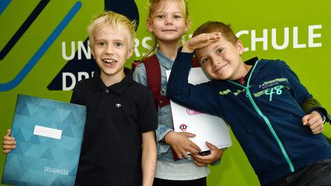 Drei Kinder stehen vor einer grünen Wand in der Universitätsschule Dresden und halten ihr Zeugnis lachend in die Kamera.