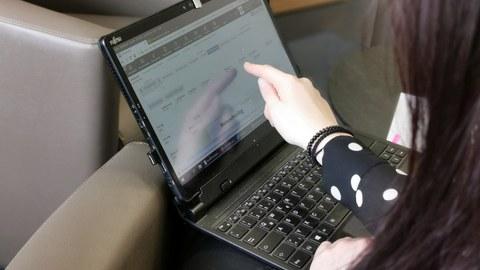 Eine Lehrerin erklärt am Laptop die Software der Universitätsschule Dresden fürs Homeschooling. Man sieht sie von hinten und ihre Hand zeigt auf den Bildschirm.