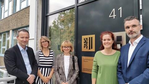 5 Personen stehen vor dem Haupteingang der Universitätsschule: der Bildungsbürgermeister, die Leiterin des städtischen Bildungsbüros, die Schulleiterinnen und ein Vertreter des Elternrats.