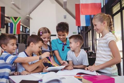 6 Kinder sitzen und stehen um einen Tisch in einer Schulbibliothek. Sie schauen auf ein Tablet.