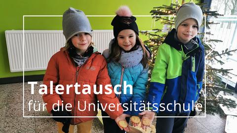 Drei Kinder in Winterjacken stehen im Foyer der Universitätsschule Dresden. Sie halten Plätzchen in Form des TU Dresden-Logos in die Kamera. Im Hintergrund steht ein beleuchteter Weihnachtsbaum.
