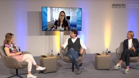 Bei einer Podiumsdiskussion sitzen zwei Schulleiterinnen und der Moderator gemeinsam im Studio. Auf einem großen Bildschirm ist Anke Langner, wissenschaftliche Leiterin der Universitätsschule Dresden zugeschaltet.