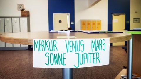 """An einem Stehtisch für die Corona-Anmeldung im Foyer der Universitätsschule Dresden klebt ein Zettel mit Stammgruppennamen als Aufschrift """"Merkur Venus Mars Sonne Jupiter"""". Im Hintergrund sind blaue Lernraumtüren und orangefarbene Spinde."""