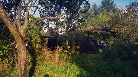 Im Schulgarten der Universitätsschule Dresden stehen zwischen alten Bäumen die großen schwarzen Zelte des Zeltlagers für die Jugendschule 2021.