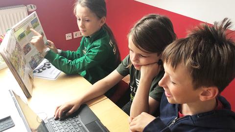 An einem Tisch sitzen drei Jungen und lernen. Einer zeigt den anderen zwein im Lehrbuch etwas. Die beiden Jungen im Vordergrund schreiben am Laptop.