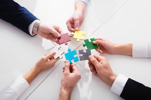 Aus der Vogelperspektive: 6 Hände halten jeweils ein großes farbiges Puzzleteil zu einem Kreis zusammen.