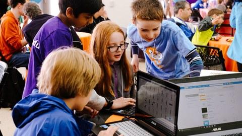 Kinder schauen beim Workshop zum Programmieren mit Scratch gemeinsam auf einen Laptop-Bildschirm.