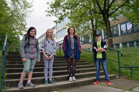 3 Schülerinnen und eine Studentin stehen auf der Treppe vor dem Schulgebäude