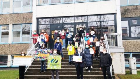 Auf der Treppe vor dem Schulgebäude steht die Delegation mit dem Spendenscheck, Million-Pixel-Bild und der Mappe mit den Unterschriften