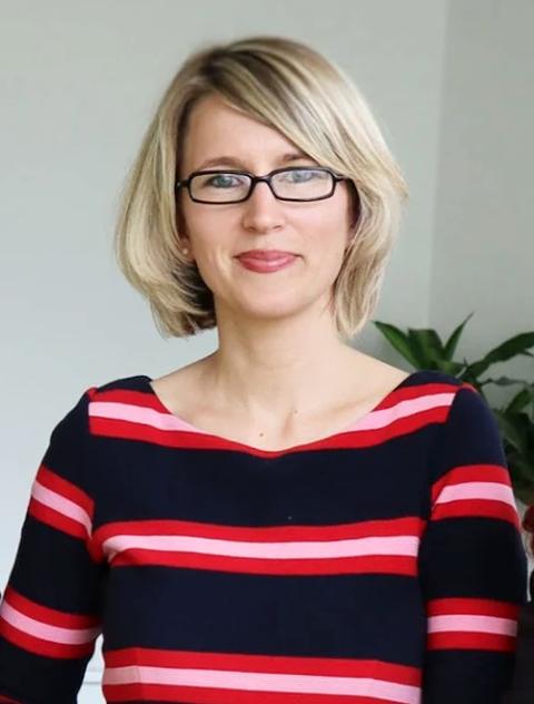 Portrait Maxi Heß, Schulleiterin der Universitätsschule Dresden, eine blonde Frau im dunkelblau und rot quer gestreiften Oberteil mit Brille.