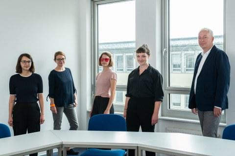 Foto der Mitarbeiterinnen und Mitarbeiter des TP I im Büro, stehend hinter Tischen und vor einem Fenster, 5 Personen
