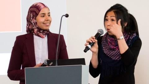 Youmna Fouad und Mei-Chen Spiegelberg tragen vor, stehen hinter einem Pult, Mei-Chen spricht in ein Mikrofon