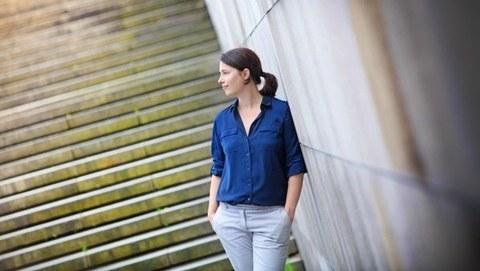 Foto von Sabine Müller-Mall, stehend vor einer Treppe angelehnt an eine Mauer, mit Händen in den Hosentaschen, nach links blickend