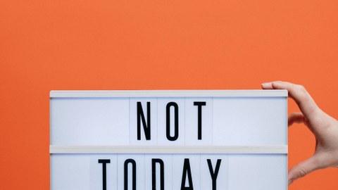 """Foto: Vor organgenem Hintergrund ist eine Holzbank abgebildet. Auf ihr steht ein Schid, auf dem """"Not Today #Covid19"""" geschrieben steht."""