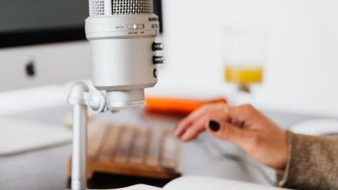 Farbfoto eines Mikrofons, welches auf einem Tisch steht. Auf dem Tisch sind ein Notizheft sowie der Auschnitt zweier Hände zu sehen.