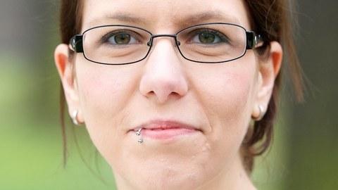 Potraitfoto von Gesine Wegner. Weiße Frau in den Zwanzigern mit Brille vor grünem, leich verschwommenen Hintergrund.