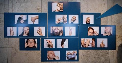 """Foto der Ausstellung """"Schmähung Provokation Stigma"""" 2020 in der SLUB, zu sehen mehrere Gesichter und Hände mit beleidigenden Gesten und Grimassen"""