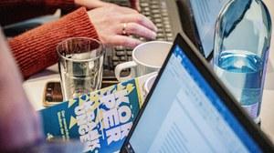 Foto von der Tagung Körper-Kränkungen, eine Hand tippt auf einem laptop, ein Flyer und ein weiterer Monitor sind zu sehen