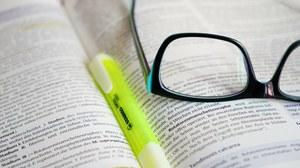 Neon-Marker und Brille auf einem offenen Buch