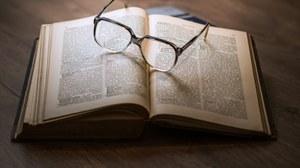 offenes Buch mit darauf liegender Brille
