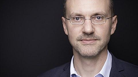 Prof. Junker (ab Schulter aufwärts) vor schwarzem Hintergrund. Herr Junker trägt eine Brille, ein hellblaues Hemd und einen dunkles Jacket.