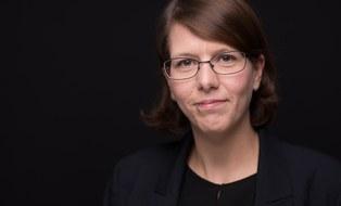 Frontalbild von Gesine Wegner vor schwarzem Hintergrund. Gesine Wegner trägt einen blauen Blazer und lächelt leicht.