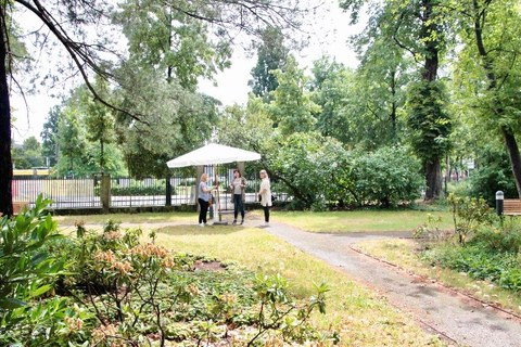 A parasol is on a green meadow. Three women are standing under the sunshade. Branches of trees reach into the picture.