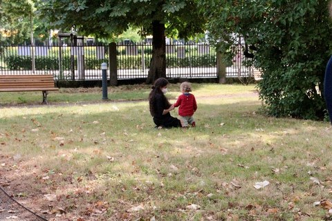 A woman is kneeling on a meadow. A child next to her is showing her something.