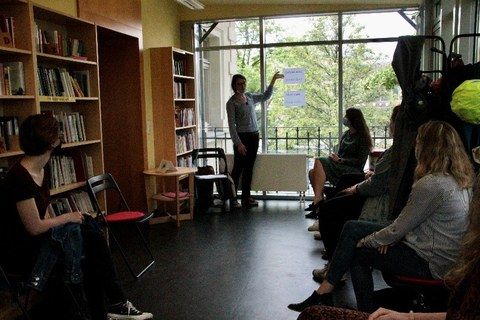 In a room with many bookshelves, people sit on chairs and listen to a woman standing at the window showing something.