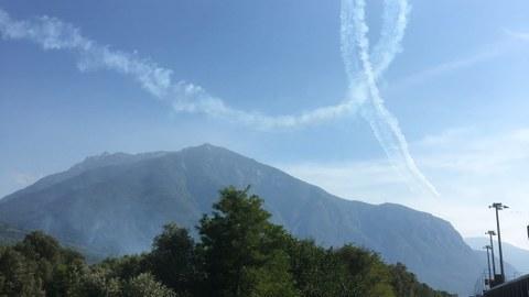 Fahrradweg mit Blick auf einen Berg. Darüber hat ein Flieger ein Looping in den Himmel gezeichnet.