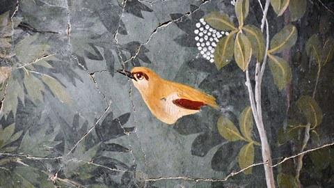 Altes Fresko eines golden leuchtenden Vogels in einem Garten