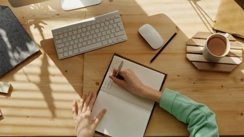 Jemand notiert etwas in ein Notizbuch, das auf einem Schreibtisch liegt. Rechts steht eine Tasse Milchkaffee. Die Sonne scheint auf den Schreibtisch. Eine Apple-Tastatur liegt vor dem Notizbuch.