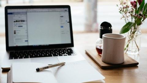 Geöffnetes Notizbuch vor Laptop