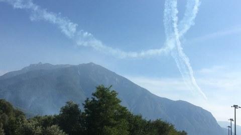 Landstraße und Berg unter blauem Himmel mit Kondensstreifen in Schleifenform bei Trento, Italien
