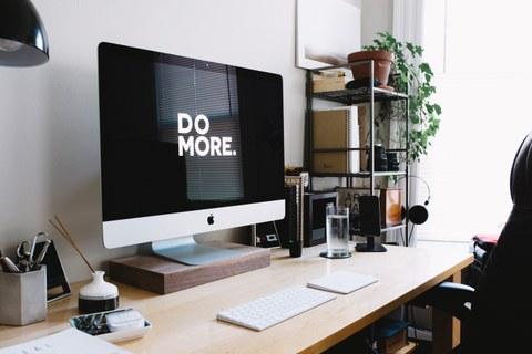 """Schreibtisch mit Mac auf dem """"Do More"""" angezeigt wird"""