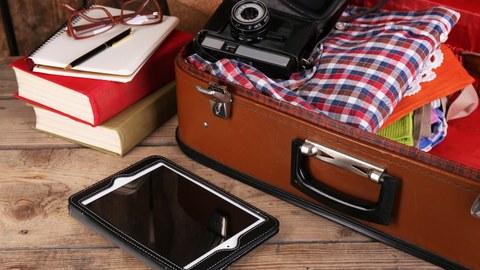 Das Foto zeigt einen braunen Koffer. In dem Koffer befinden sich Kleidung und eine alte Kamera. Davor liegt ein Tablet. Außerdem erkennt man Bücher, ein Notizbuch und eine Brille.