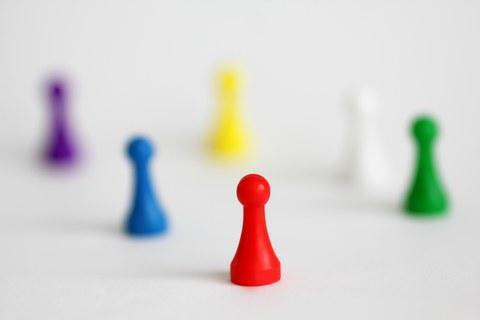 Bunte Spielfiguren stehen auf einem weißen Tisch