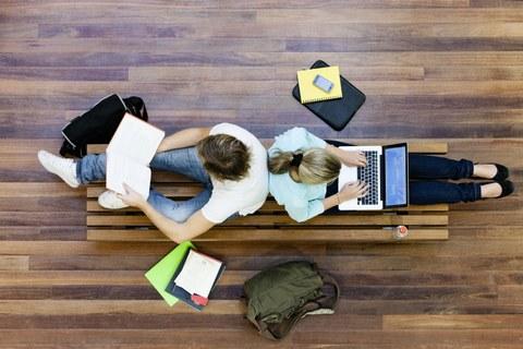 Zwei Studierende sitzen mit Büchern und Laptop am Fußboden