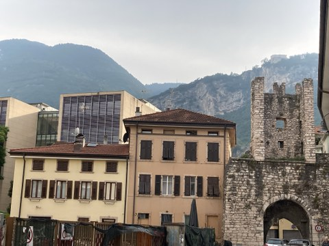Blick auf einen mittelalterlichen Turm, daneben ein Haus, dahinter das Fakultätsgebäude und ganz im Hintergrund die Berge