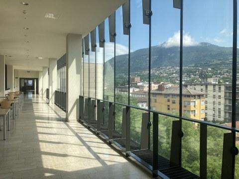 Flur im trienter Fakultätsgebäude mit Tischen entlang einer Glasfront, dahinter der Blick über die Stadt und die Berge